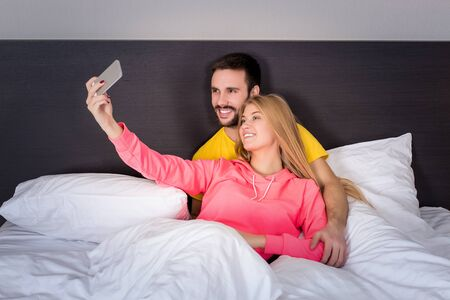 woman relaxing: Young happy couple on bed  doing selfie with telephone camera. Concept about technology and people