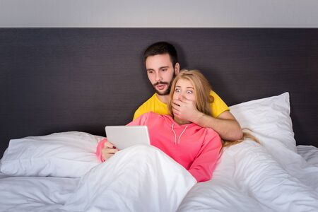 adult couple: Young Sweet Couple on Bed Watching Something on Tablet Gadget. Concept about technology and people Stock Photo
