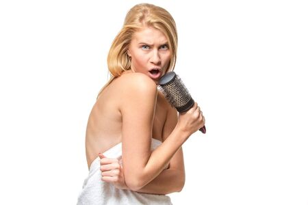 suntanned: Happy pretty woman in towel singing using comb having fun, isolated on white. Stock Photo