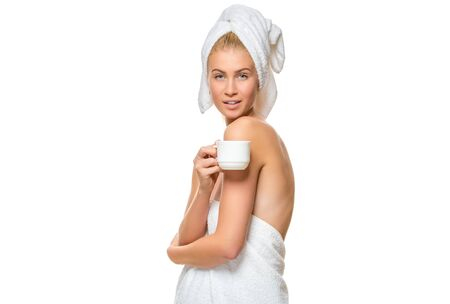 suntanned: Young attractive woman with blue eyes in a towel drinks from a cup, eyes closed on white background.