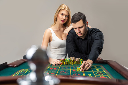 Men with women playing roulette at the casino. Man placing a bet at the casino Stock Photo