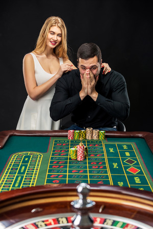 wins: Couple playing roulette wins at the casino. Addiction to the gambling