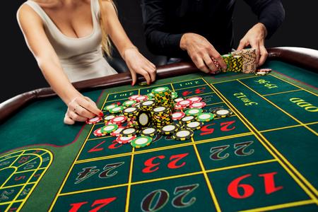 Paar spelen roulette wint in het casino, het gokken spaanders genomen door de handen vrouw. Detailopname