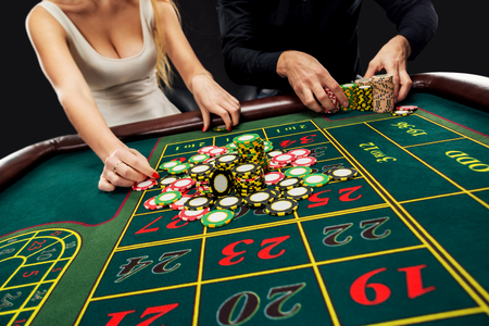 Couple playing roulette wins at the casino, gambling chips taken by hands woman. Closeup