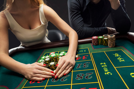 wins: Couple playing roulette wins at the casino, gambling chips taken by hands woman. Closeup