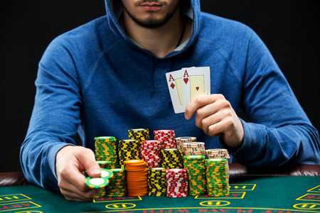 poker player: Poker player sitting at a poker table with chips and showing a pair of aces. Closeup