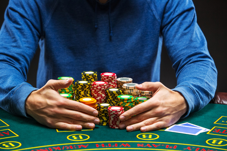 poker: Poker player sitting at a poker table taking poker chips after winning. Close up