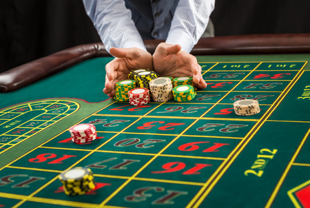 Picture of a green table and betting with chips. Man hand over casino chips  - bet. Close up Stock Photo