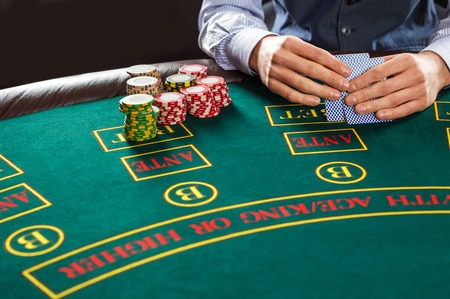 texas hold em: Close up of poker player with playing cards and chips at green casino table.