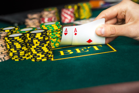 Close-up of male poker player lifting the corners of two cards aces at green casino table with aces Stock Photo
