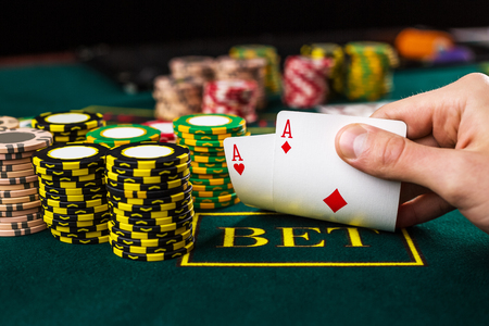 Close-up of male poker player lifting the corners of two cards aces at green casino table with aces Stockfoto
