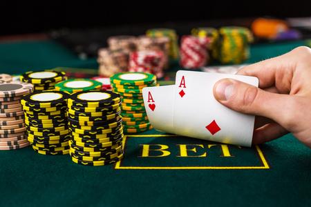 Close-up van mannelijke pokerspeler waarbij de hoeken van twee kaarten azen op groen casino tafel met azen Stockfoto