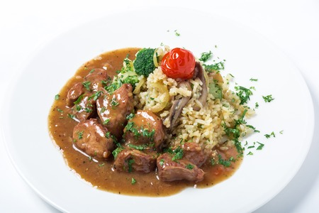 gourmet food: La carne de pavo con arroz, br�coli, champi�ones y salsa verdes decoradas en un plato blanco. De cerca Foto de archivo