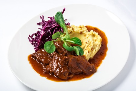 Cooked veal cheeks in gravy with potatoes and cabbage, decorated fresh herbs in white plate. Close-up Stock Photo