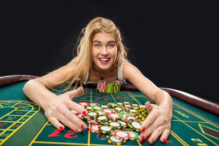 glamour couple: Young pretty women playing roulette wins at the casino, gambling chips taken by his hands