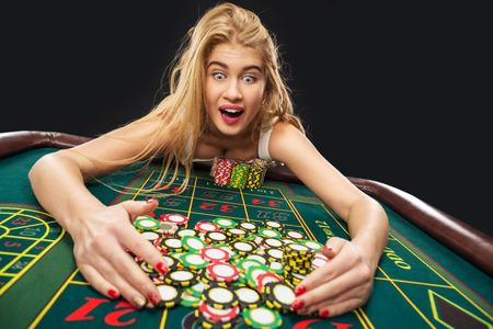 roulette: Giovani donne graziose che giocano vittorie roulette al casinò, fiches prese dalle sue mani