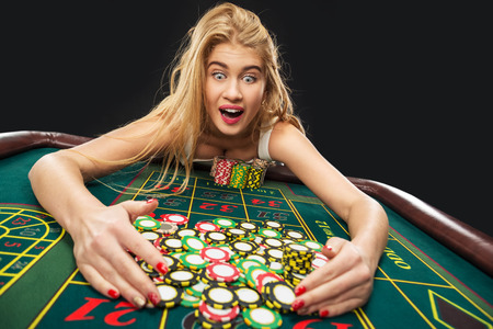 Young pretty women playing roulette wins at the casino, gambling chips taken by his hands