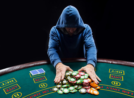 poker player: Poker player sitting at a poker table trying to hide his expressions and going all-in pushing his chips forward