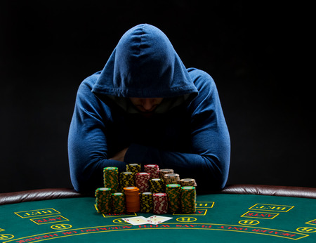 poker player: Portrait of a professional poker player sitting at a poker table with poker chips trying to hide his expressions