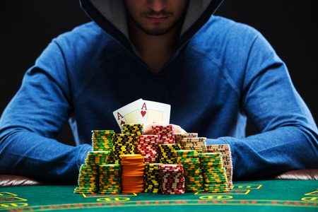 aces: Poker player sitting at a poker table with chips and showing a pair of aces. Closeup