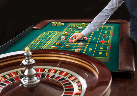 fortune: Roulette and piles of gambling chips on a green table in casino. Man hand over casino chips on roulette table