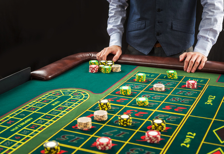 roulette table: Picture of a green table and betting with chips. Man hand over casino chips on roulette table. Close up Stock Photo