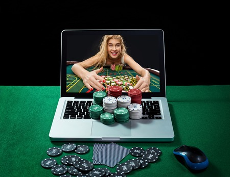 poker player: Green table with casino chips, cards on notebook, image of poker player on screen of laptop. Concept for online gambling