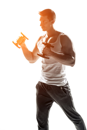 solar flare: Handsome muscular man doing exercises with dumbbells isolated on white background  Whith solar flare Stock Photo