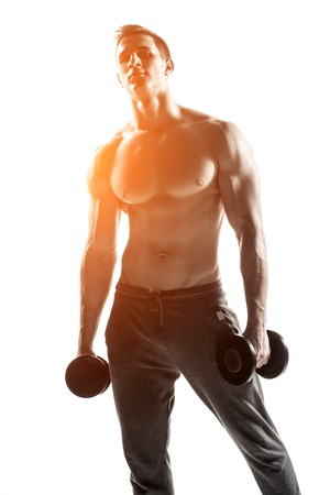 solar flare: Strong athletic man showing muscular body with dumbbells, isolated on white background.  Whith solar flare Stock Photo