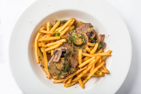 french fries plate: Roast pork on toast with mushrooms and sauce, served with french fries in white plate. Close-up top view