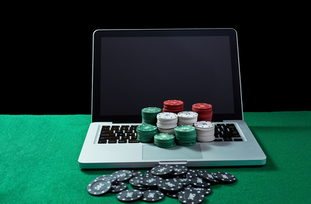 Image of casino chips on a keyboard notebook at green table. Concept for online gambling, poker, virtual casino.