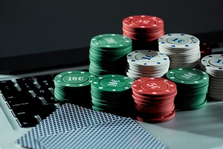 View of casino chips and cards on a laptop to play online. Concept for online gambling, poker, virtual casino. Stock Photo
