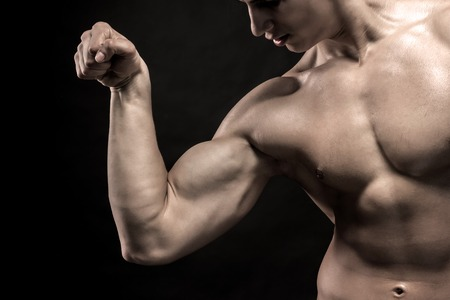 naked male body: Close-up of young man flexing and showing his triceps and biceps muscles on black background Stock Photo