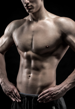 naked male body: Close-up of a power fitness man. Strong man with muscles and biceps on black background