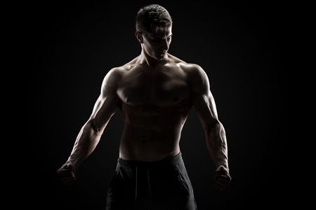 Sexy muscular man posing with naked torso in studio and looking behind on black background