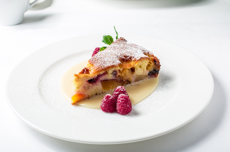 Piece of delicious clafoutis with nectarine and plum, served with raspberry in white plate. Close-up Stok Fotoğraf