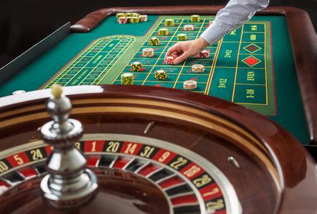 Roulette e pile di gettoni da gioco su un tavolo verde in casinò. Man mano sul chip del casinò sul tavolo della roulette