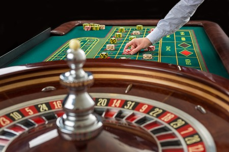 Roulette and piles of gambling chips on a green table in casino. Man hand over casino chips on roulette table