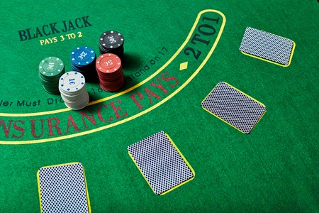 casino table: Casino chips and deck of cards lying on green casino table, poker game concept, top view.