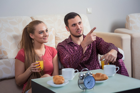 Cute young couple relaxing at home on the floor beside the couch having breakfast, eating croissants and drinking orange juice.