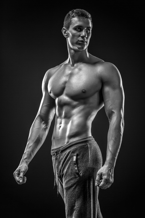 nude male body: Image of very muscular man posing with naked torso in studio and looking behind on black background. Black and white