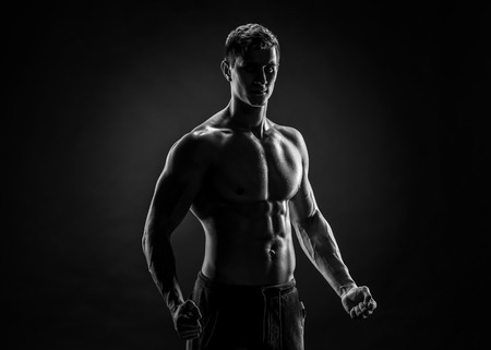 Sexy shirtless bodybuilder posing and looking at camera on black background. Extreme strength, muscles and fitness.. Black and white Stock Photo