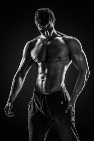 silueta masculina: Sporty and healthy man posing and showing his perfect boddy on black background. Black and white