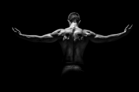 Rear view of healthy muscular young man with his arms stretched out on black background. Black and white