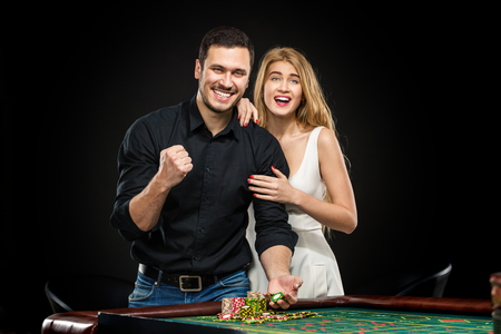 roulette table: Young couple celebrating win at roulette table in casino, girl embracing man