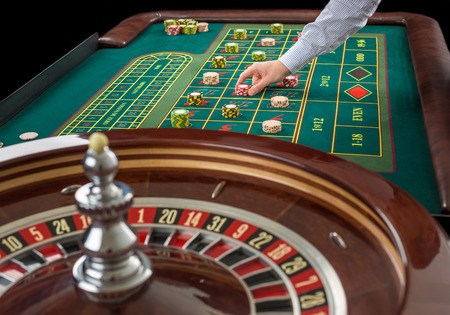 Roulette and piles of gambling chips on a green table in casino.  Man hand over casino chips  - bet. Stock Photo