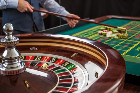 croupier: Roulette and piles of gambling chips on a green table in casino. Croupier collects chips using stick