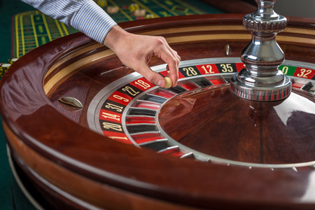 fortune: Roulette wheel and croupier hand with white ball in casino close up details