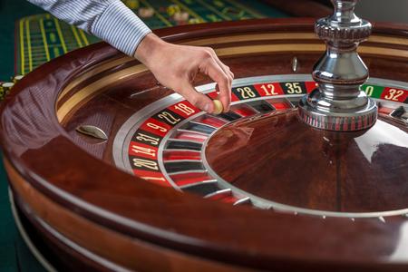 rueda de la fortuna: rueda de la ruleta y de la mano con la bola blanca croupier en el casino de cerca los detalles Foto de archivo