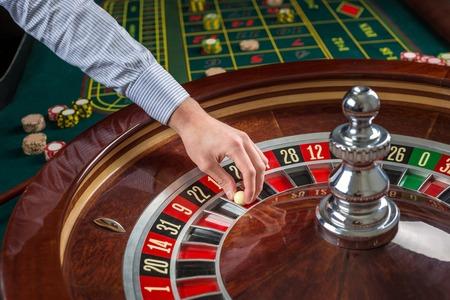 Roulette wiel en croupier de hand met witte bal in het casino close up details